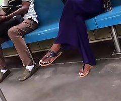 Tan girl crossed legs in flip flops